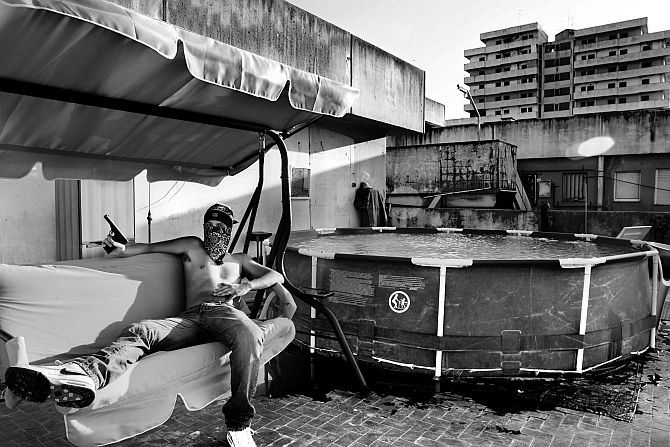 Naples, Scampia neighborhood, a large area under Camorra control, the biggest area in Europe known for drug selling. A pusher with his gun on the roof of a building called The Sails