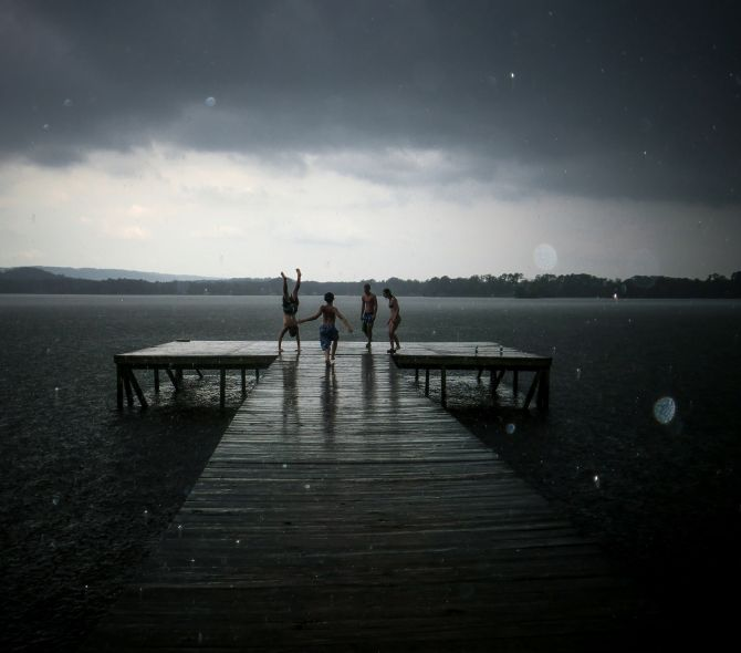 In your youth, nothing can stop you from enjoying time with your friends, especially not a simple matter of rain during summer fun. You may grow up and forget the names, but you'll always remember the moments, the time on the dock with your friends during a surprise shower.