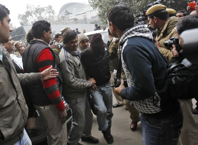 Plain-clothes police escort a man (face covered) accused of a gang rape outside a court in New Delhi