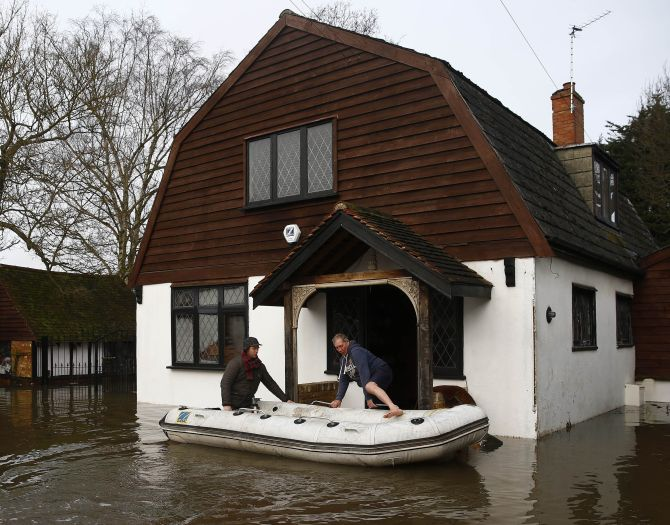 A resident is rescued from his house after the river Thames flooded the village of Wraysbury, southern England, on Monday.