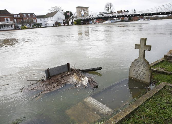 The river Thames floods into a graveyard at All Saints church in Marlow, southern England