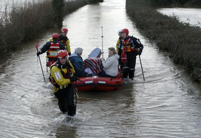 Residents are rescued by the Devon and Somerset Fire and Rescue service during continued flooding at Burrowbridge in south west England.