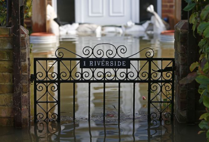 The front gate to a house is seen surrounded by water after the river Thames flooded the village of Wraysbury, southern England, Monday