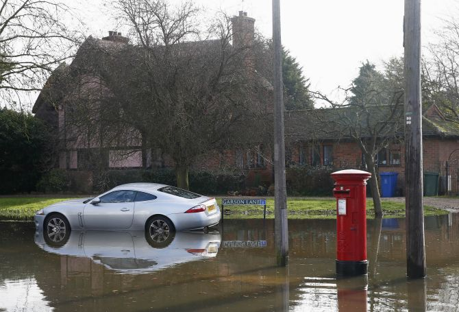 A car is seen surrounded by water after the river Thames flooded the village of Wraysbury, southern England.