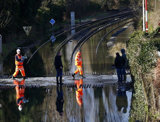 Railway workers are seen crossing the tracks after the river Thames flooded the railway in the village of Datchet, southern England.