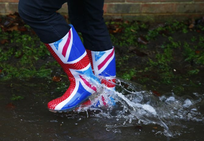 A resident's Wellington boots are seen splashing through water after the river Thames flooded the village of Wraysbury, southern England