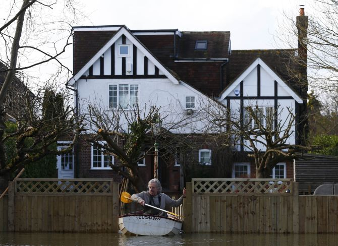 Nigel Gray leaves his home in a rowing boat after the river Thames flooded the village of Wraysbury, southern England