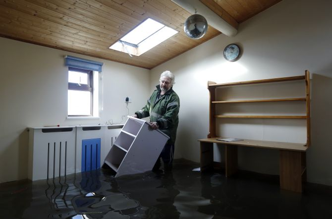 Resident, builder Dave Donaldson moves furniture from one of the flooded rooms of his home at Burrowbridge on the Somerset Levels in south west England