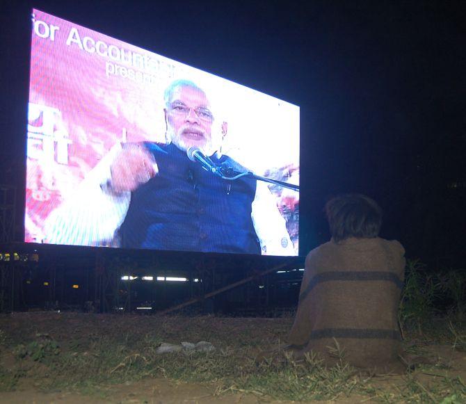 A lone street kid watching Narenda Modi's address on a giant screen at Karnavati Park