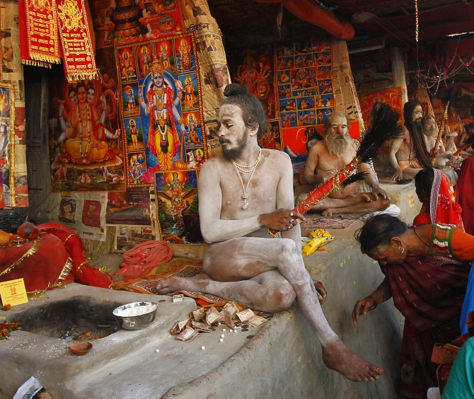 A Hindu woman seeks a Naga sadhu's blessings in Kolkata.