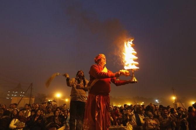 A Hindu priest performs evening prayers on the banks of the Ganga.