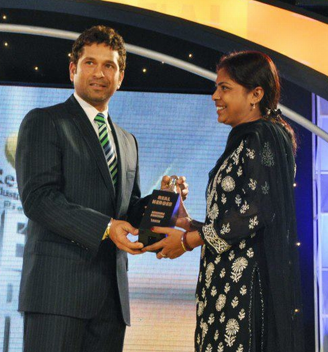 Naseema receives an award felicitating her from cricketer Sachin Tendulkar