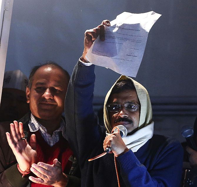 Delhi's Chief Minister Arvind Kejriwal shows his resignation to his supporters while addressing them from his party headquarters in New Delhi on Friday