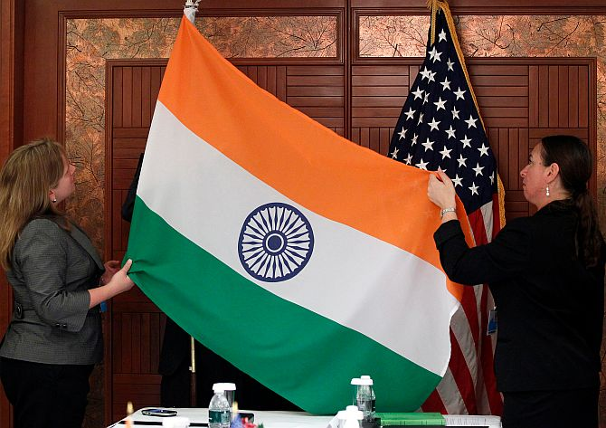 India and US flags arranged before a media briefing.