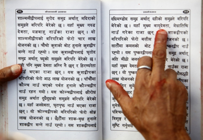 A Hindu holy man holds the holy book on his hand as he recites verses