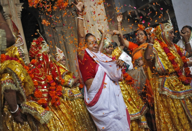 A woman throws flower petals and dances with widows dressed as Krishna's consort, Radha, during celebrations to mark Janmashtami festival at the Meera Sahavagini ashram in Vrindavan