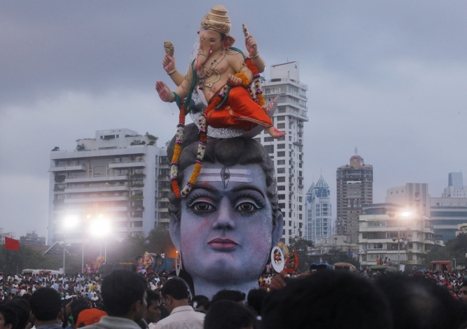 Devotees watch idols of Ganesh, and Lord Shiva as they are placed on the seashore before immersion on the last day of Ganesh Chaturthi, in Mumbai.