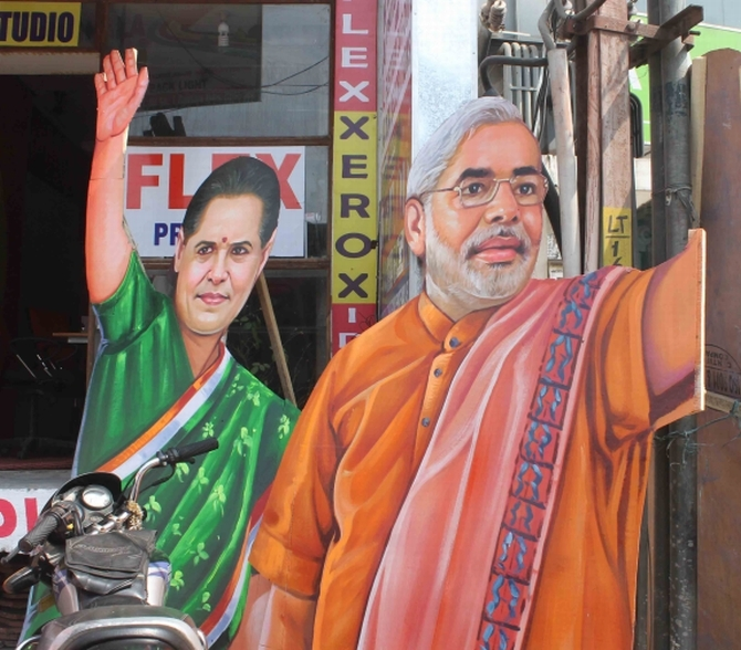 Cut-outs of Congress President Sonia Gandhi and BJP's PM candidate Narendra Modi at a political rally