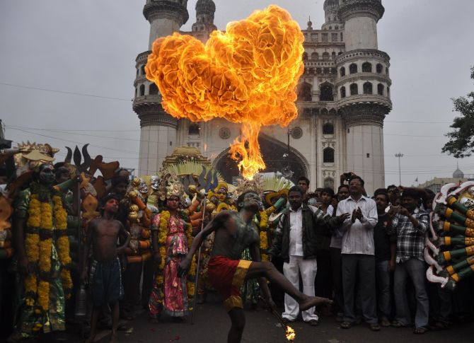 A performer blows fire from his mouth during Bonalu celebrations in Hyderabad