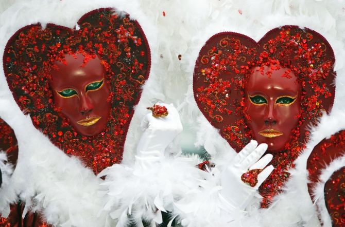 A couple wear masks in the shape of a heart while posing for tourists in Saint Mark's square during the carnival in Venice.