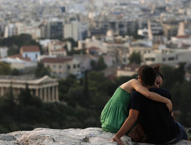 A couple embraces as they sit on a hill overlooking Athens near the archaeological site of the Acropolis in Athens.
