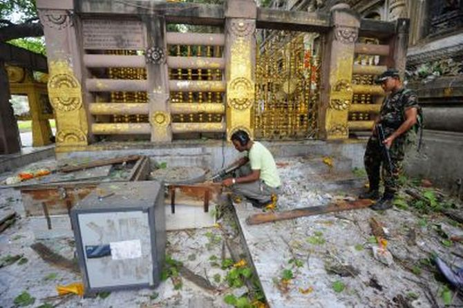 Security personnel inspect the site of an explosion inside the Mahabodhi temple complex at Bodh Gaya.