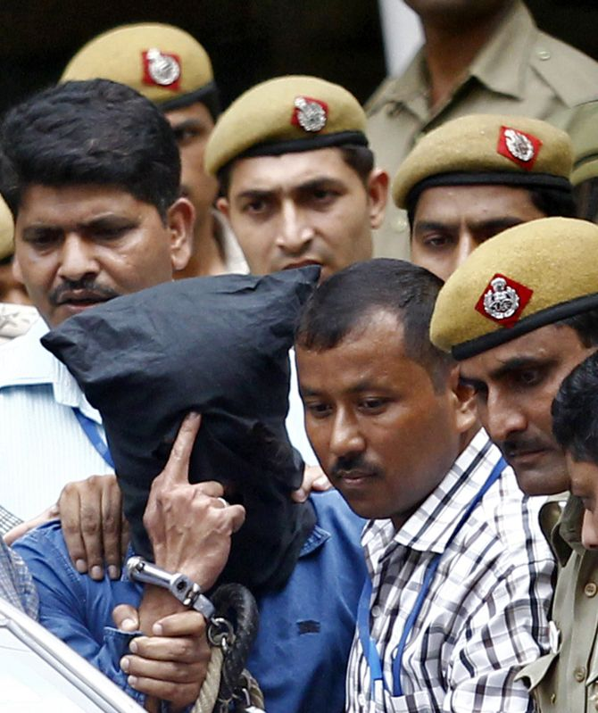 Police escort Yasin Bhatkal (head covered), the key operative of the Indian Mujahideen militant group, outside a court in New Delhi