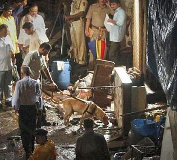 Police use a sniffer dog at the site of an explosion in the Zaveri Bazaar, south Mumbai