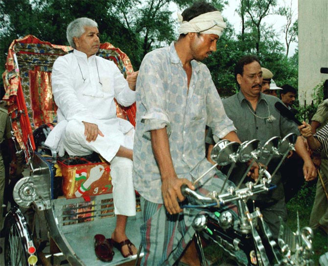 Former Bihar chief minister Laloo Yadav arrives in a rickshaw to appear before a court for his involvement in the fodder scam in Patna, October 1998.