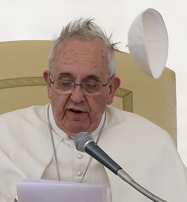 A gust of wind blows Pope Francis's skull cap off during his general audience in Saint Peter's square