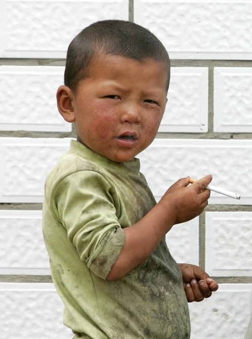 An ethnic Tibetan boy smokes a cigarette, which he had asked from a man (not pictured), at Sangke grassland in Xiahe, western China's Gansu province.