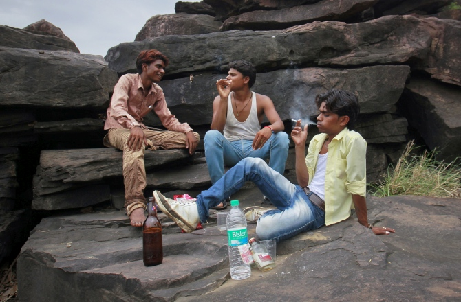 Gopal Kishan (right), 15, smokes a cigarette as he drinks with his friends on the outskirts of their village near Kota, located in Rajasthan.