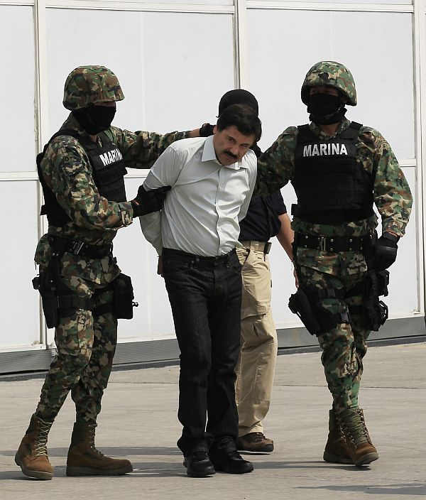 Joaquin Shorty Guzman is escorted by soldiers during a presentation at the Navy's airstrip in Mexico City
