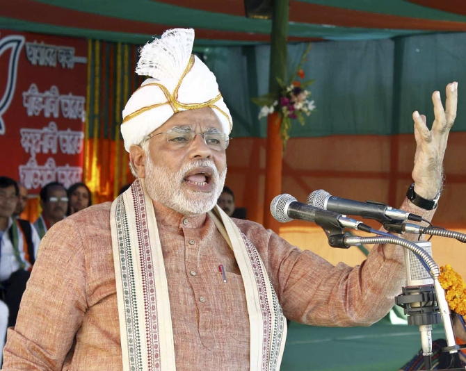 Modi wears a koyet, a head-dress of Manipur's Meitei community, and an ethnic shawl as he delivers a speech at Ramnagar in Silchar, Assam.