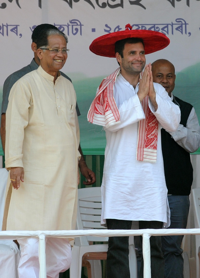 Congress Vice President, wearing a traditional Assamese hat and shawl, greets his supporters at a rally in Guwahati, as CM Tarun Gogoi stands by his side