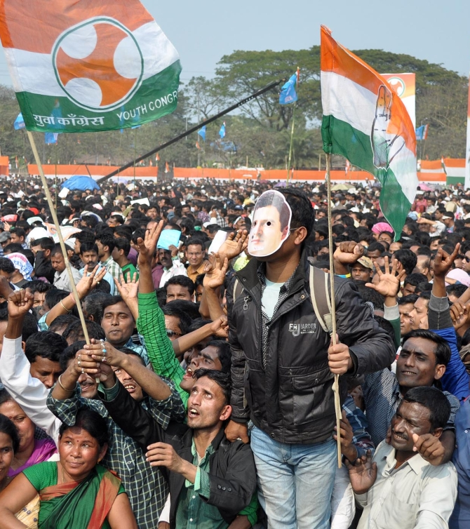 A Congress supporter wears a mask of Rahul at the rally