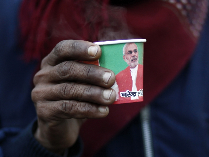 A man holds a paper cup carrying a portrait of Modi during a 'chai pe charcha' initiative in Delhi recently
