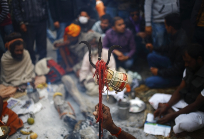 A hand of a Sadhu holds a trident at the premises of a temple during the Shivaratri festival.