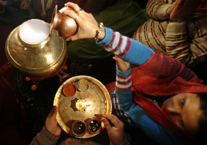 A Kashmiri woman pours milk into a sacred pot during Mahashivratri in Srinagar.