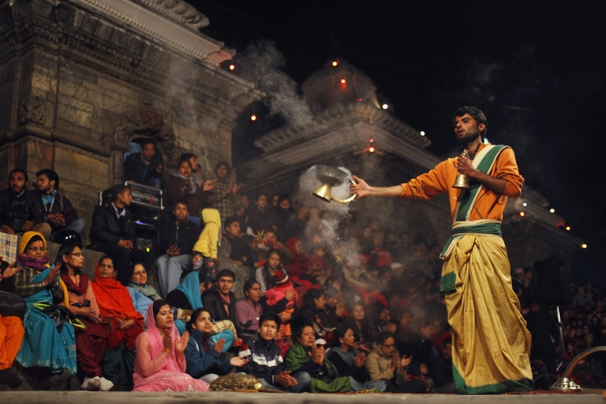 A priest offers an evening prayer as devotees sing holy songs on the eve of Shivaratri festival at the premises of a temple.