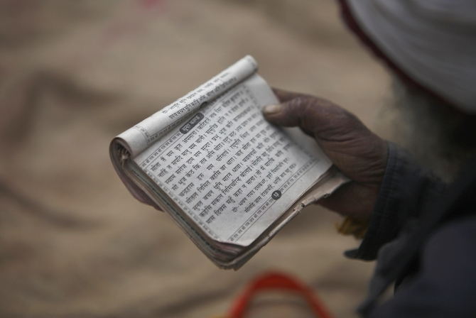 A holy man recites prayers from a holy book at the premises of a temple.