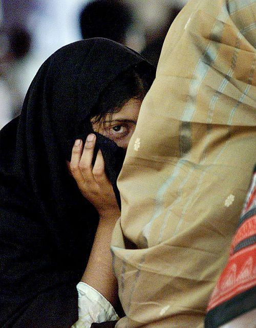 A girl hides from the camera during a sit-in in to protest against communal violence