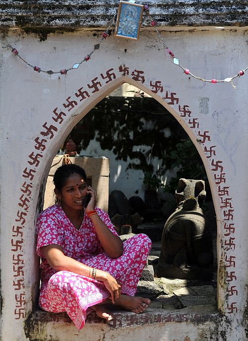 An Indian housewife speaks on her mobile phone as she sits outside her home in Mumbai