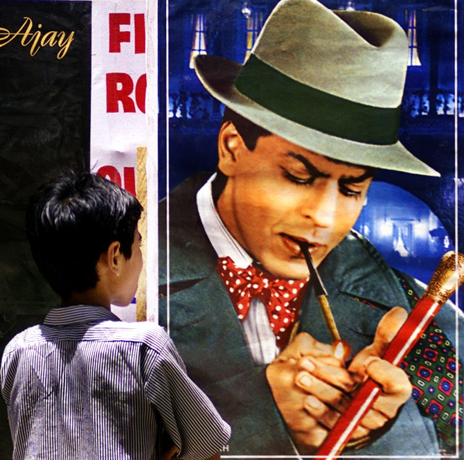A boy looks at a poster of Bollywood actor Shah Rukh Khan smoking a cigarette during an anti-tobacco demonstration in Mumbai.