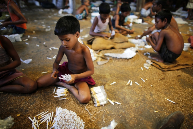 Children fill up empty cigarettes manually with locally grown tobacco in a small bidi factory at Haragach in Rangpur district, Bangladesh.