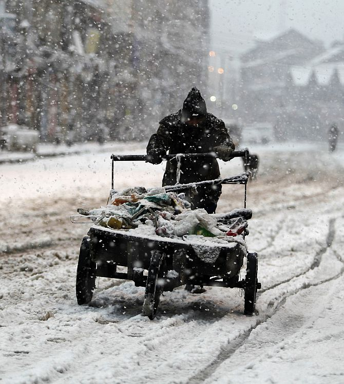 A man pushes his handcart through a snow-covered street during snowfall on a cold winter morning in Srinagar