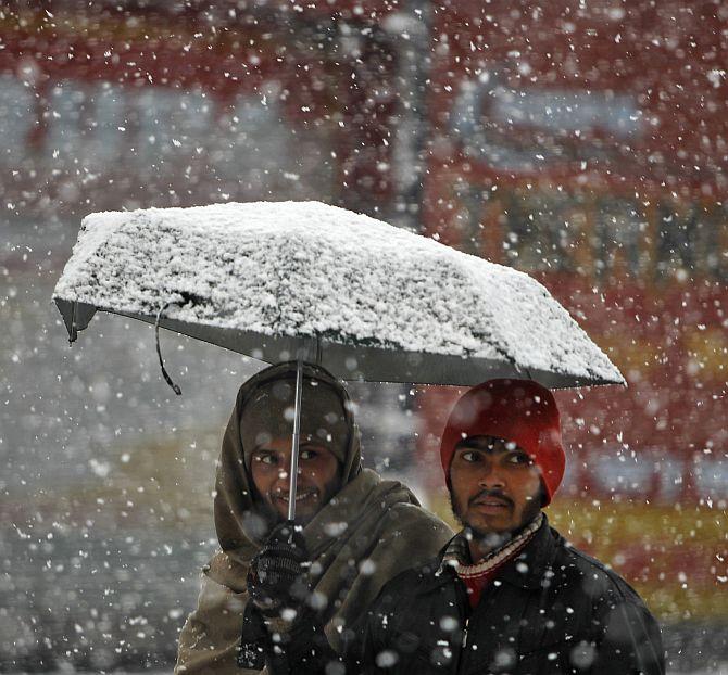 Men walk under an umbrella during snowfall on a cold winter morning in Srinagar