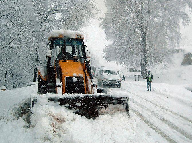 An earthmover clears snow off the Srinagar-Jammu National Highway