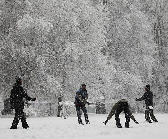 Tourists enjoy a snowball fight during snowfall on a cold winter morning in Srinagar