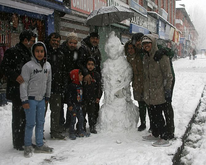 Tourists pose with a snowman in Srinagar